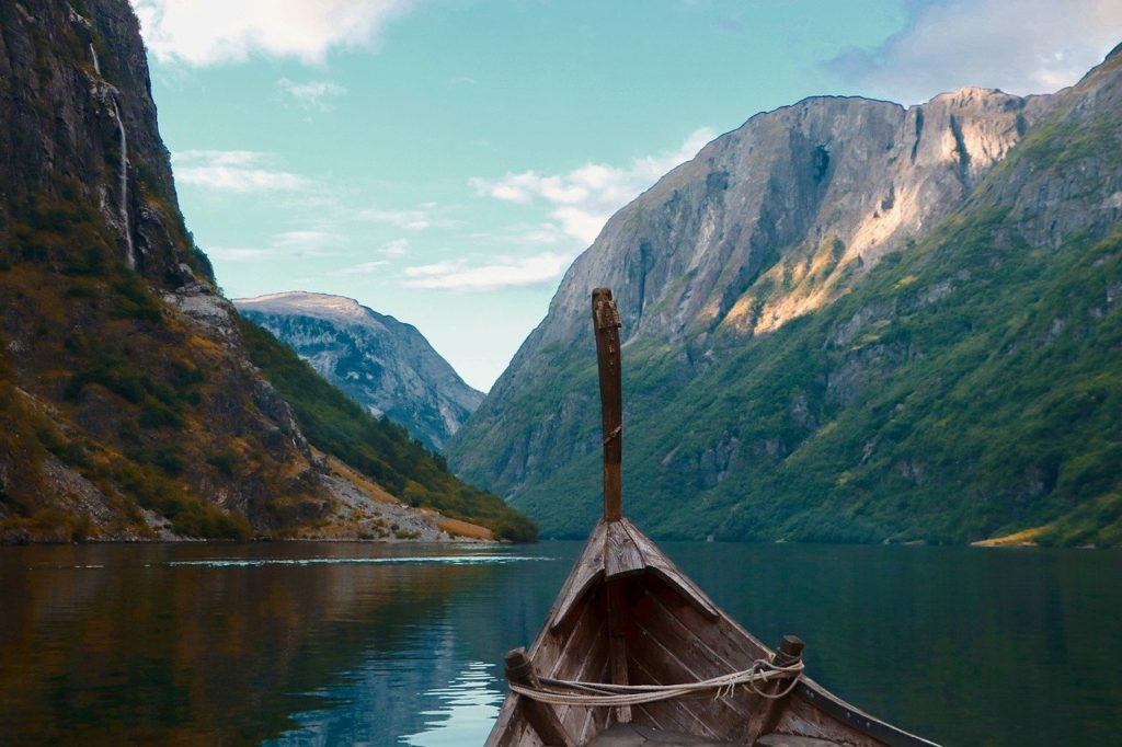 bow of a Viking boat representing colonization in Greenland, with mountains in the background